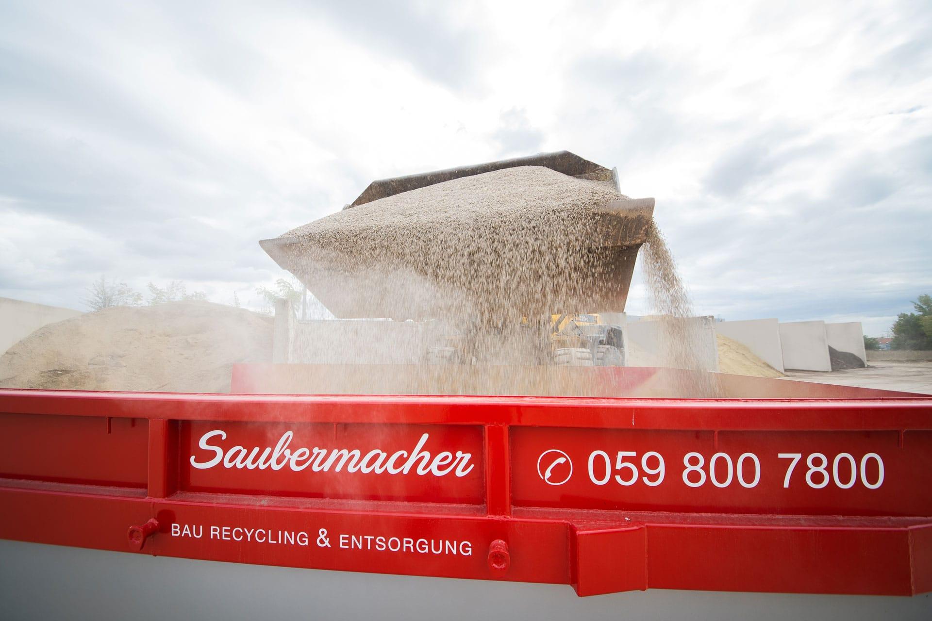 Sand wird in einen Saubermacher-Baurecycling-Container geleert
